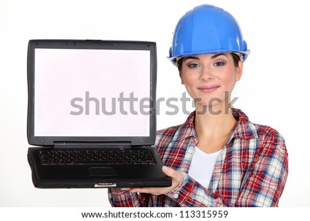 A female construction worker presenting a laptop.