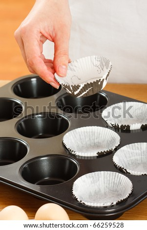 A female cook 's hand putting  muffin cups in the oven pan. - stock photo