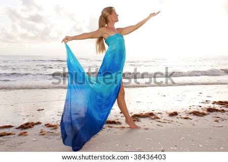 a female dancer is posing in profile with arms raised and looking at her open hand at the beach with waves crashing in the background - stock photo