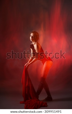 A female dancer posing with red cloth, creating streaks of light due to long exposure and mixed lighting.