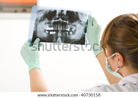 A female dentist examining a panoramic radiography. - stock photo