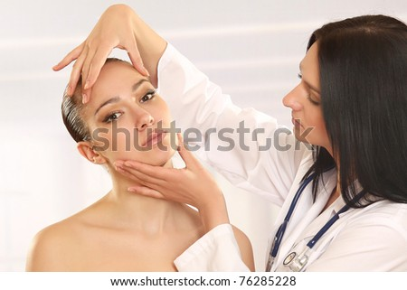 A female doctor examining her patient - stock photo