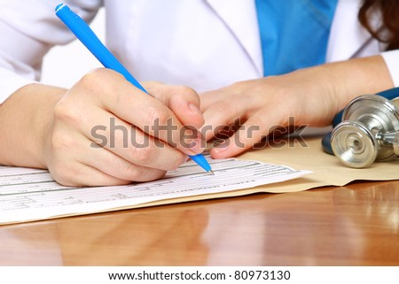 A female doctor is fiiling a prescription - close-up - stock photo