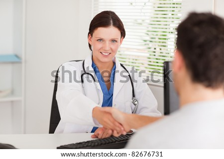 A female doctor is shaking hands with a patient in her office