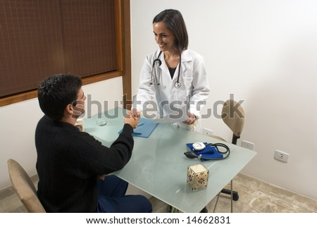 A female doctor is smiling and shaking hands with her patient.  The doctor and the patient are looking at each other.  Horizontally framed photo. - stock photo