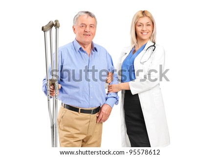 A female doctor or nurse holding a senior patient with crutches isolated on white background - stock photo