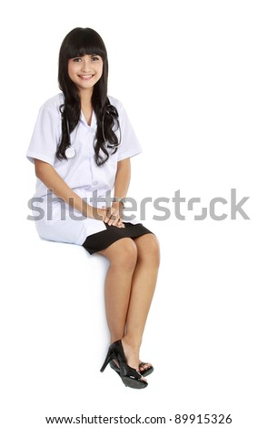 A female doctor sitting in a blank space isolated over white - stock photo