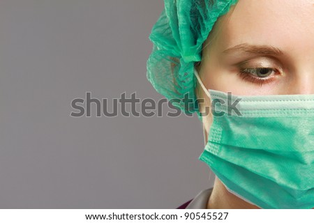 A female doctor wearing a mask, isolated on grey background - stock photo