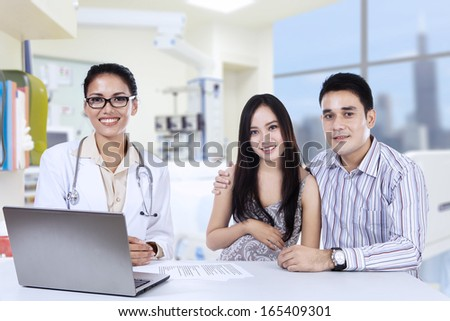 A female doctor with laptop and happy asian couple in doctor's office - stock photo
