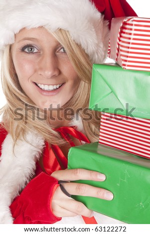 A female dressed like santa is peeking around some presents. - stock photo