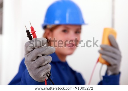 A female electrician holding a voltmeter.