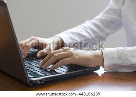 A female employee is working on a laptop computer