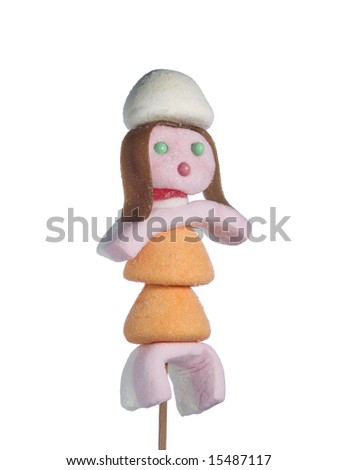 A female figurine made out of candies on a stick over a white background.