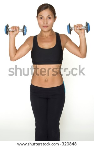 A female fitness instructor demonstrates the starting position of the standing dumbbell press
