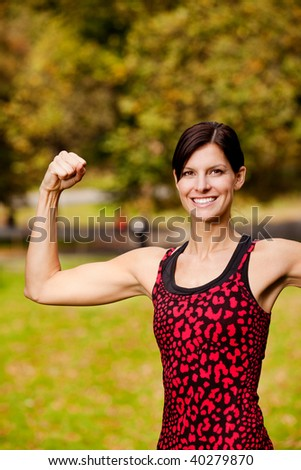 A female fitness model flexing her bicep - stock photo