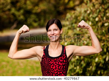 A female fitness model flexing her biceps - stock photo