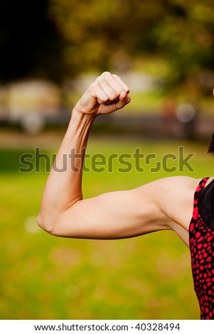 A female flexing her bicep muscle - stock photo