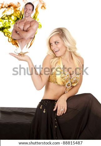 a female genie holding her golden lamp in her hand with smoke and a man coming out of the lamp. - stock photo