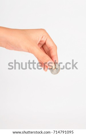 A female hand hold a coin isolated white