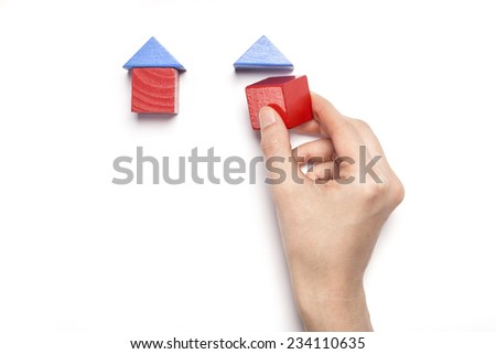 A female hand hold(pick up) the wood blocks like house(real estate) isolated white, top view at the studio. - stock photo