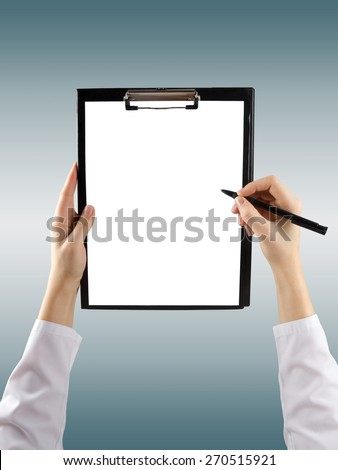 A female hand holding a pen and clipboard with blank paper (document, report) on blurred background. Top view - stock photo
