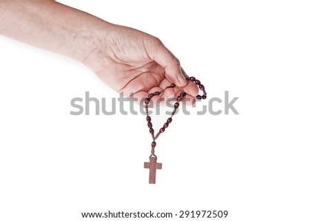 A female hand holding brown wooden rosary on a white background