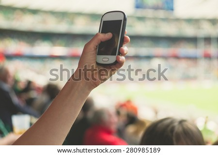 A female hand is holding a smart phone in a stadium to take pictures of a sporting event - stock photo