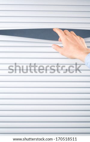 A female hand opening venetian blinds from the inside.