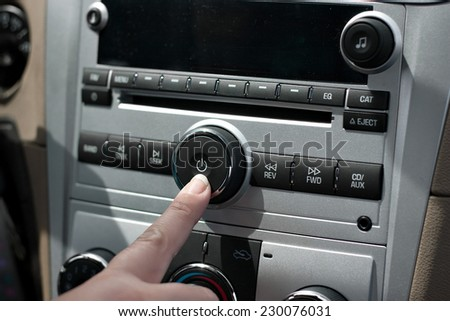 A female hand pushing the power button to turn on the car stereo system.