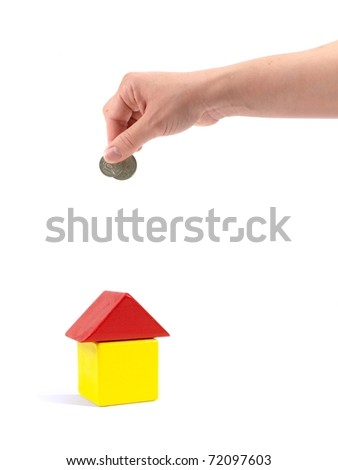 A female hand with coin and a toy house isolated against a white background - stock photo