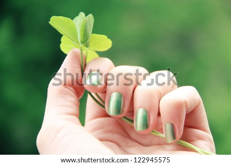 A female hand with spring green (mint coloured) nail polish on holding a clover twig against a green background