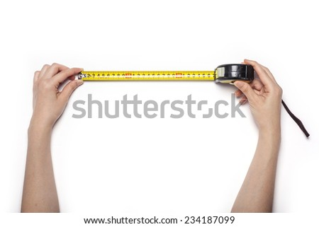 A female hands hold a yellow tape measure isolated white, top view at the studio. - stock photo