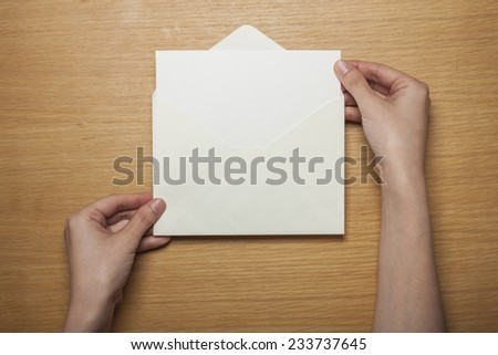 A female hands hold(grip) a white envelope and postcard on the wooden desk, top view at the studio. - stock photo