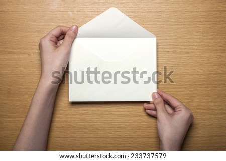 A female hands hold(grip) a white envelope on the wooden desk, top view at the studio. - stock photo