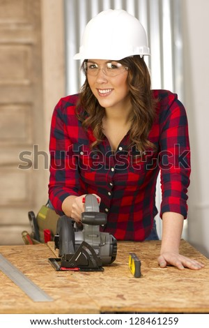 A female handy woman works on a building project in the shop sawing cutting boards - stock photo