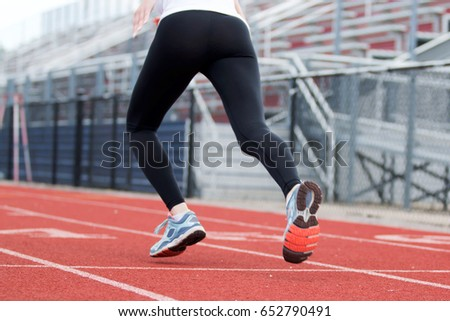 A female high school track runner starts her sprint down the track
