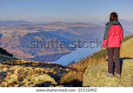 A Female hiker looking down on Thirlmere from the Wythburn path to Helvellyn - stock photo