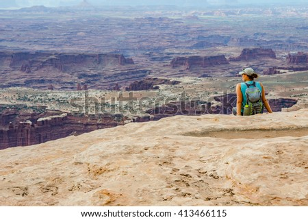 A female hiker looks out over a vast canyon on a hike in Utah - stock photo
