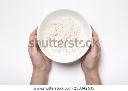 A female hold a bowl with Vietnam rice noodles isolated white, top view at the studio. - stock photo