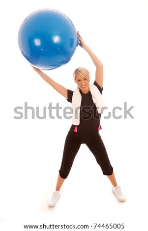 A female holding a blue gym ball above her head
