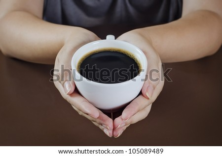 a female holding a cup of coffee on the table - stock photo