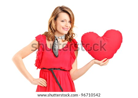 A female holding a red heart shaped pillow isolated on white background - stock photo