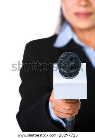 A female host is holding a microphone pointed directly to the camera. Shot against white background. - stock photo