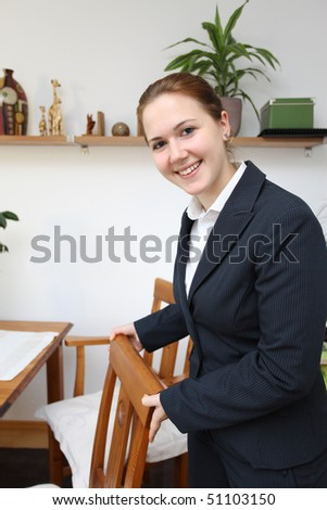 A female hotel manager offering a seat - stock photo