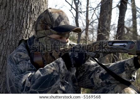 a female hunter aiming her shotgun - stock photo