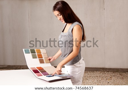 A female interior architect or designer looking at rug samples from a catalogue - stock photo
