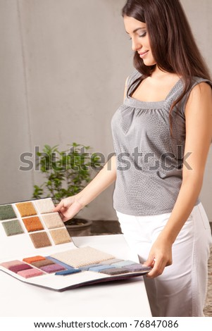 A female interior designer looking at carpet swatches in a catalogue - stock photo