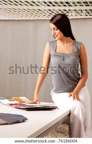 A female interior designer looking at rug samples from a catalog - stock photo