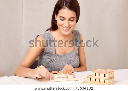 A female interior designer working on a scale model - stock photo