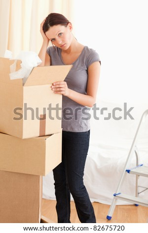 A female is packing a cardboard in the living room